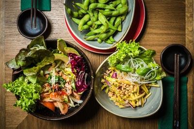 Salate und Edamame auf dem Tisch